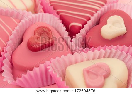 Close-up of a pink heart shaped petit fours cakes seen from the side on a pink background