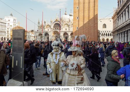 Venice, Italy - February 19 2017: Carnival mask and costume couple poses. Masked couple in traditional costume pose at PIazza San Marco before the Basilica during the Venice 2017 Carnival.