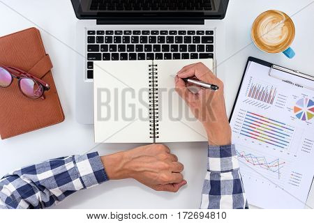 Businessman hands with pen writing notebook on office desk table. Business analysis and strategy concept.Top view