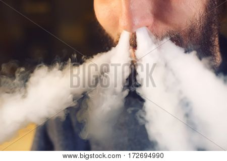 The man smoke an electronic cigarette at the vape shop.