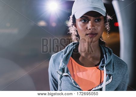 Close up shot of beautiful fitness woman in the city at night. African female in sportswear looking at away