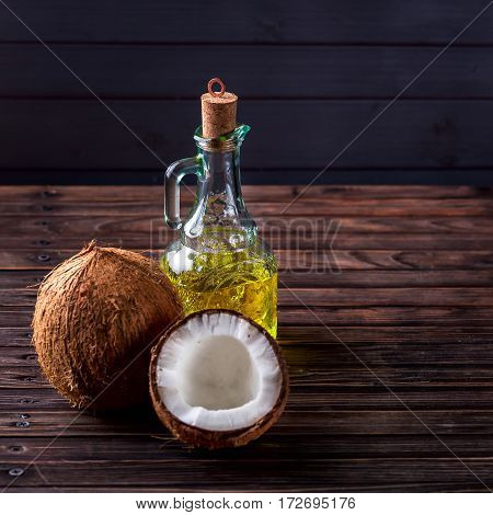 Coconuts on a dark wooden background. Glass bottle with oil nearby. Concept of health and beauty