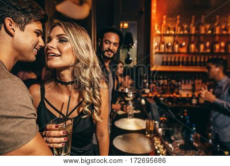 Romantic young couple at nightclub. People having great time at pub.