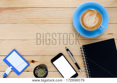 Office desk table with leather notebookblank screen smart phonepen name card and cup of coffee.Top view with copy space