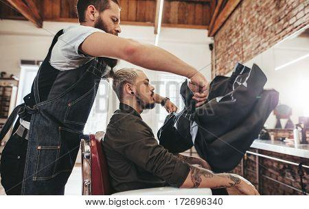 Barber Putting Salon Cape To Client