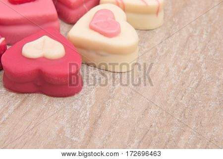 Close up of heart shaped petit fours cakes seen the side on a wooden background