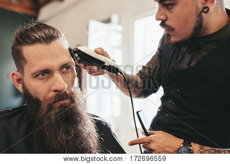 Young Man Getting Trendy Haircut At Salon