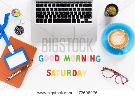 Caption word Good morning saturday. White office desk with laptop diary eyeglasses compass pen blank identification card and cup of coffee on white background.