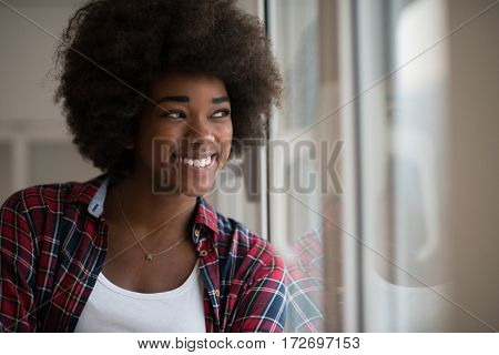 portrait of a young beautiful African American woman with curly hair near the window