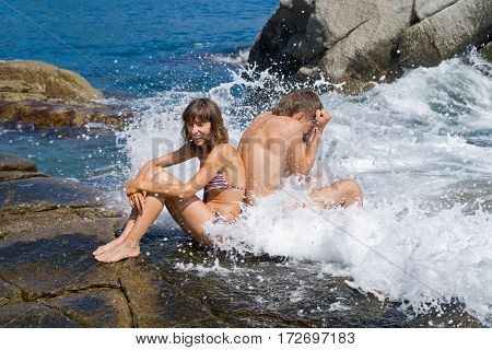 The young man and woman on reefs in surf.