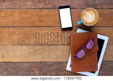 Office desk table with leather notebooksmart phonetableteyeglasses and cup of coffee.Top view with copy space.Working desk table concept.