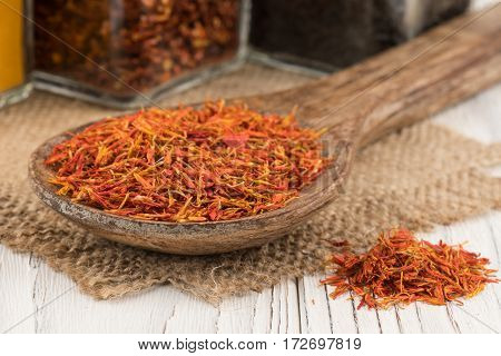 Saffron in a wooden spoon and an old white wooden table. Selective focus.