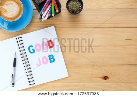 Caption word Good job. Office desk with notebook pen color pencil card and cup of coffee on white background.top view with copy space