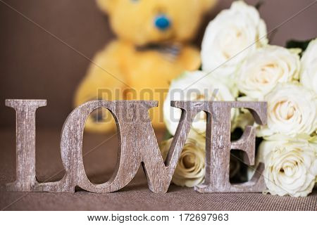 A word LOVE made of wood, flowers and a yellow teddy bear in blue bow tie background.