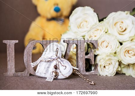 A word LOVE made of wood, a wooden decorative heart, flowers and a yellow teddy bear in blue bow tie background.