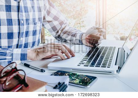 Hipster man hands holding a credit card and using smart phone for online shopping.Online shopping concept.