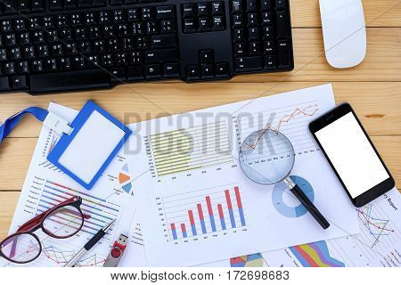 Office desk table with smart phonepenname card mouse glasseskeyboard and business chart or graph.Top view with copy space.Business analysis and strategy concept.