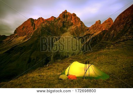 Last glow of daylight hits the mountain peaks. The warm and illuminated tent promises a comfortable night.