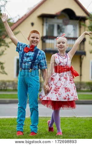 Boy and girl in dancing suits pose on grassy lawn against two-storied house.
