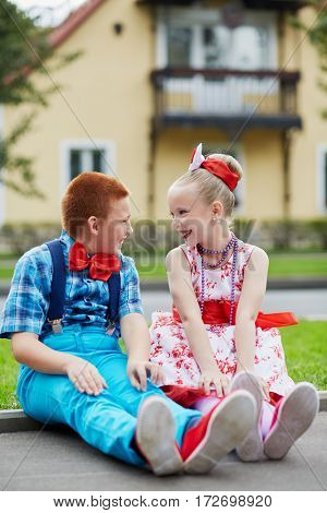 Smiling boy and girl in bright dancing suits sit on road curb and look at each other against two-storied house.