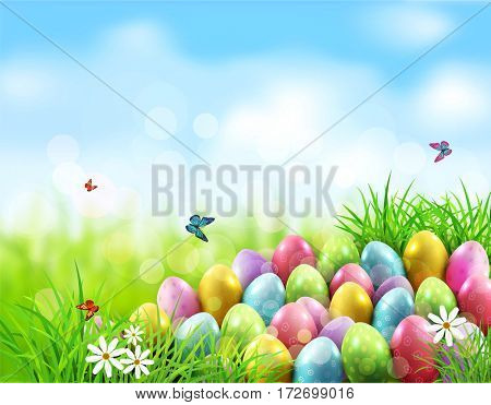 background. Easter eggs in green grass with white flowers, butterflies on blue, blurred , natural background