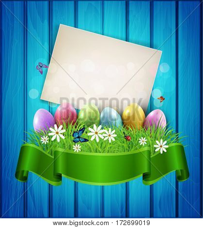 Easter Eggs with greeting card, grass and flowers in green ribbon on a blue wooden background. Element for celebratory design.