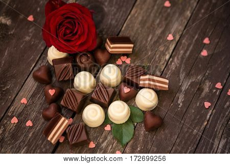 Various chocolate pralines and red roses background- Mother's Day
