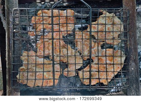 A close up of the cooking pork chops on grill.