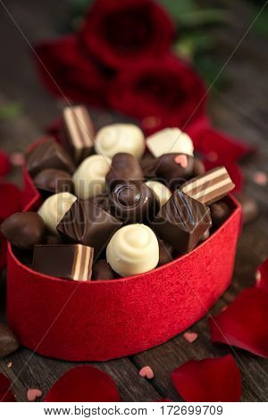 Chocolate pralines in gift box on wooden background