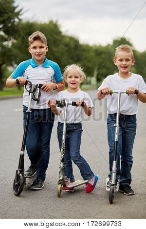 Two boys and girl in t-shirts ride on scooters on road.