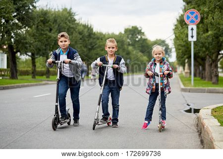 Two boys and girl stand with push scooters on road.