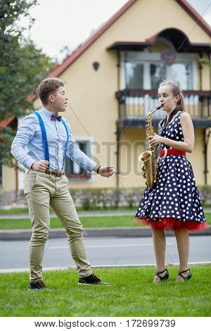 Teenage girl plays saxophone and boy dances on grassy lawn against two-storied house.