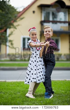 Boy and girl in dancing suits dance on grassy lawn against two-storied house.