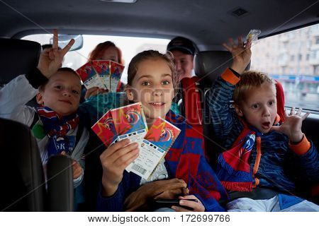 Three children and two adults in car cabin show tickets for soccer match.
