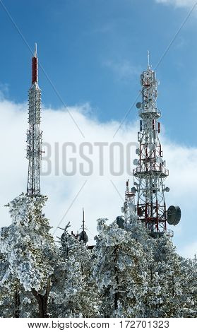 telecommunications towers covered with snow in the frosty winter background