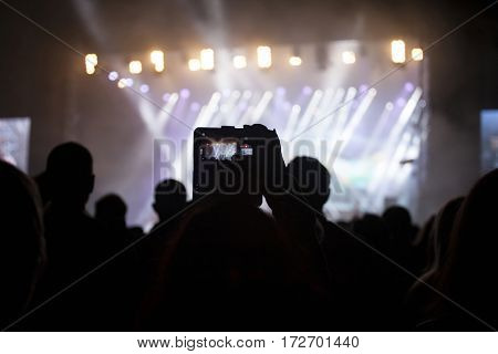 Silhouette of hands using camera phone to take pictures and videos at pop concert, festival.