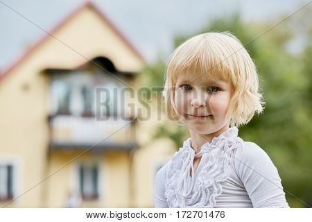 Humeral portrait of little blonde girl outdoor against house.