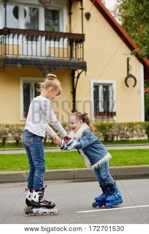 Two girls ride on roller skates in front of two-storey house.