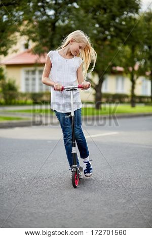 Girl with long blonde hair rides on scooter on street.