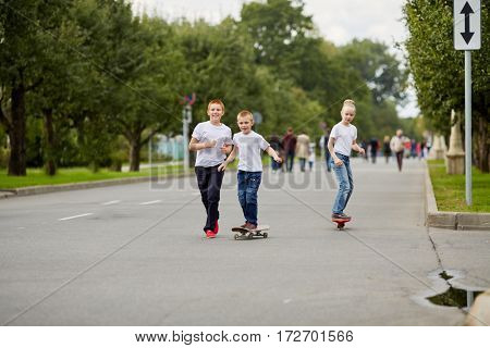 Two boys and girl ride skateboard and walk on street.