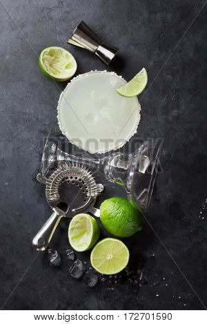 Margarita cocktail on dark stone table. Top view