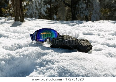 Colorful ski glasses and gloves on snow at wonderful sunny day