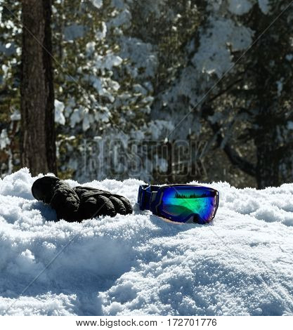 ski glasses and gloves on snow at wonderful sunny day background