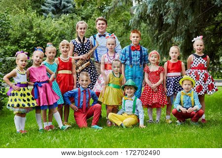 Group portrait of fifteen children dressed in bright dance suits posing at grassy lawn.