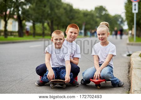 Two smiling boys and girl sit on skateboards on road.