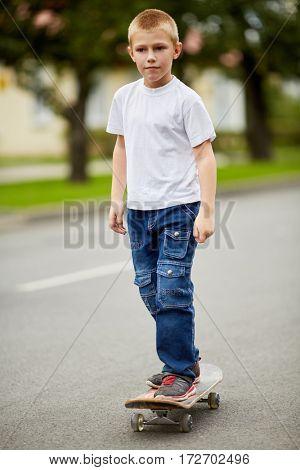 Boy rides on skateboard on street.