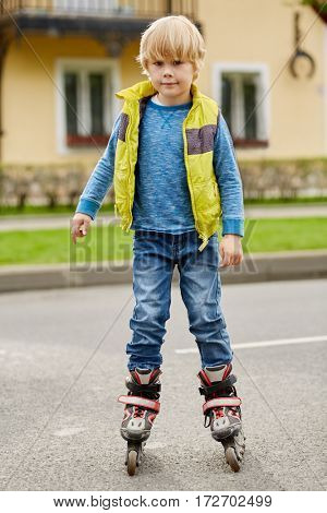 Boy on roller skates in front of house on street.