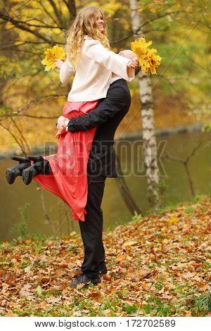Man raises young pretty woman near river in yellow autumn park