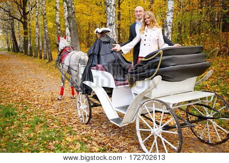 Happy couple are in coach with horse and coachman in autumn park