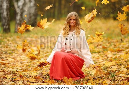 Beautiful young woman in red skirt throws up leaves in yellow autumn park
